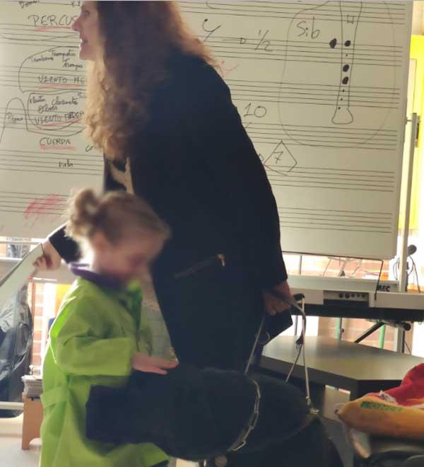 Niña en la escuela aprendiendo sobre la discapacidad y  acariciando a nuestra perrita guía Alma.