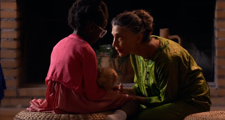 Imagen de la pelicula , Gannet de niña con su muñeca y practicando su lenguaje de signos con su madre adoptiva .