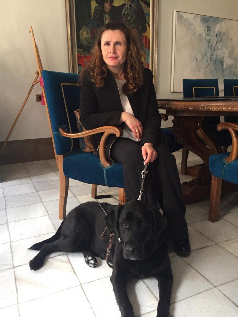 Presidenta asociación Perro guías Murcia sentada en el ayuntamiento de Cieza con Alma su perra guia